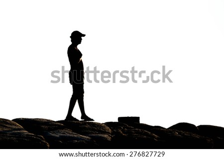 Silhouette of man standing on the rock ,on white background. Element of design. - stock photo