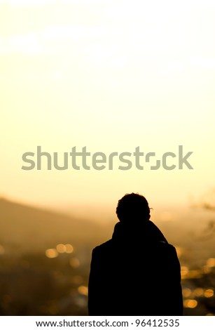 silhouette of man standing over freiburg in sunset - stock photo