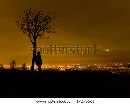 Silhouette of Man Stood By Tree Overlooking Cityscape at Night - stock photo