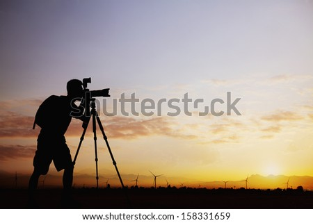 Silhouette of man taking photos with his camera at sunset  - stock photo