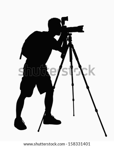 Silhouette of man taking pictures with camera on tripod. - stock photo