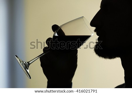 Silhouette of man tasting red wine, close-up - stock photo