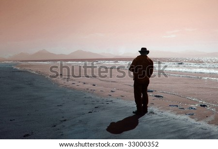 Silhouette of man walking along the water's edge on a fantasy beach - stock photo