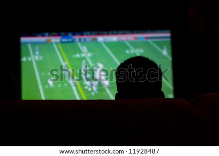 Silhouette of Man Watching Football Game on Widescreen TV - stock photo