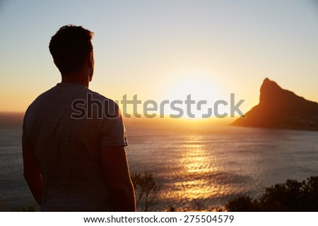 Silhouette Of Man Watching Sun Set Over Sea And Cliffs - stock photo