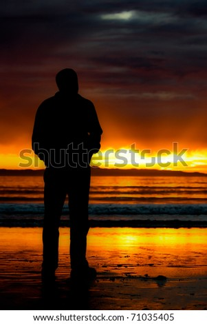 silhouette of man watching sunset - stock photo