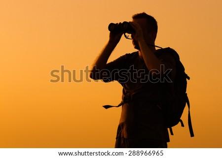 Silhouette of man watching sunset with binoculars .Hiker with binoculars - stock photo