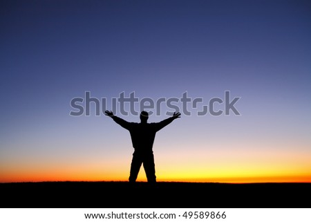 Silhouette of man with arms outstretched at sunset - stock photo