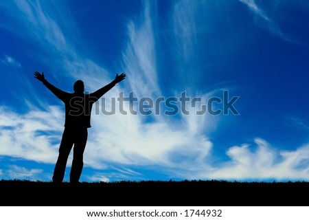 Silhouette of man with arms outstretched to the sky. - stock photo