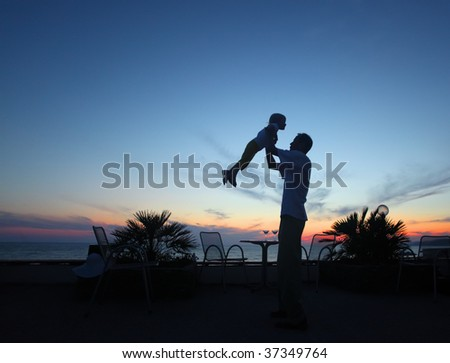 Silhouette of man with child in hands on sunset - stock photo