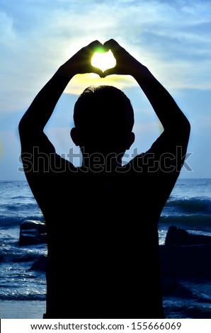 Silhouette of man with hand showing heart shape when sun rising - stock photo