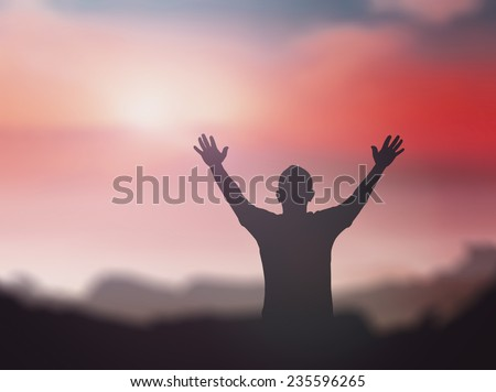 Silhouette of man with hands raised to beautiful sunset background. - stock photo