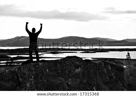 Silhouette of man with his arms stretched out to the sky. - stock photo