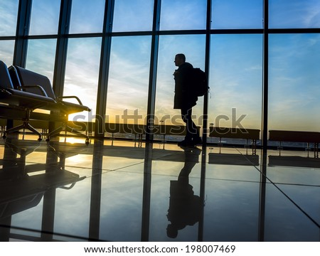 Silhouette of man with luggage standing near window in airport