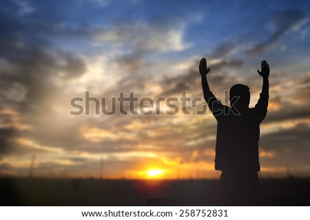 Silhouette of man with raised hands over blur nature background concept for religion, worship, prayer, praise and victory. - stock photo