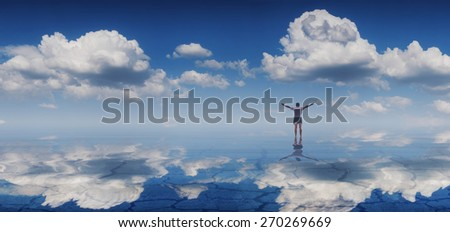 Silhouette of man with raising hands on a smooth surface of the lake, reflected in water - stock photo
