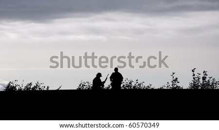 Silhouette of man with shotgun and trooper talking - stock photo