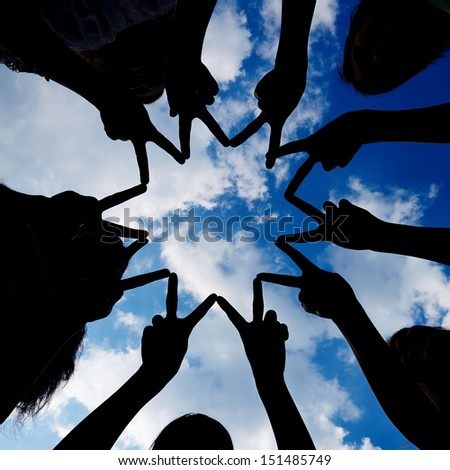 Silhouette of many hands forming star network under a sky - stock photo