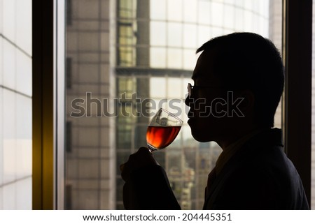 Silhouette of mature businessman drinking a glass of wine in hotel. - stock photo