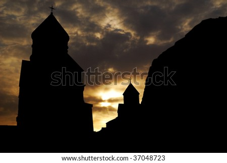 silhouette of medieval monastery against sunset sky - stock photo