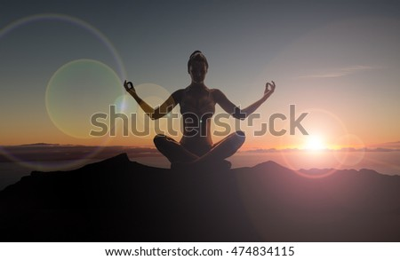Silhouette of meditating woman on the mountain