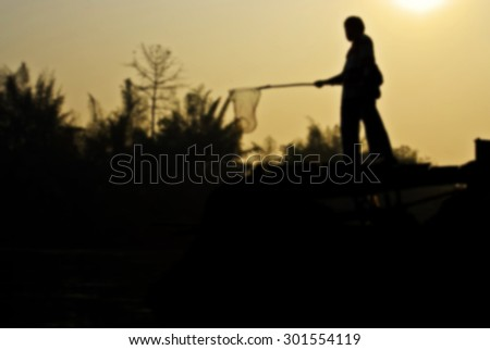 silhouette of Men fishing of landscape during sunrise, blur background