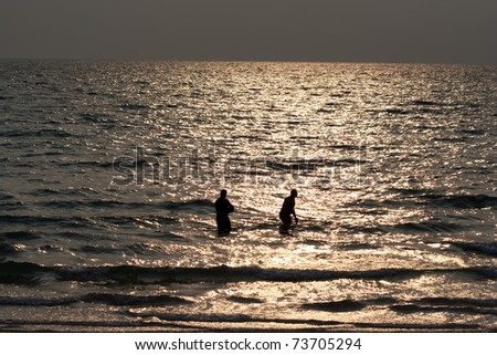 Silhouette of men in the sea at a beach. - stock photo