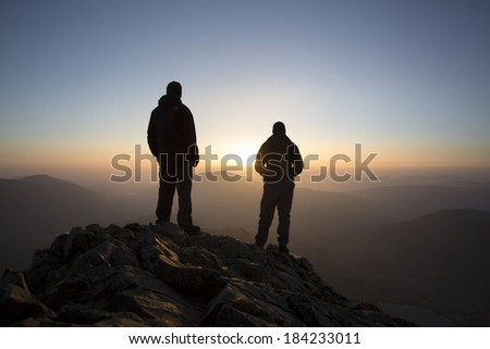 silhouette of 2 men on a mountain at sunrise, crib goch, snowdon - stock photo