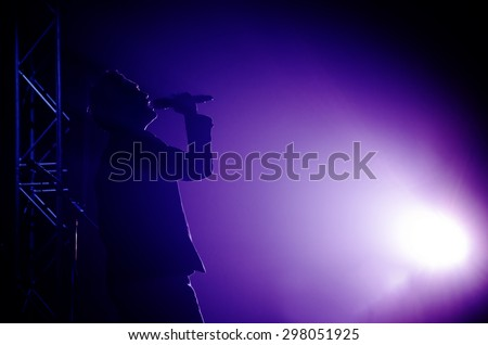 silhouette of men singing , live concert on stage - stock photo