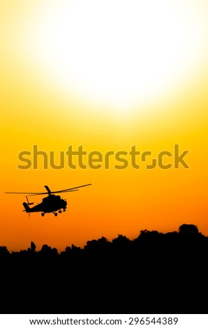 silhouette of military helicopter above the ground - stock photo