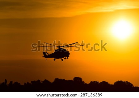 silhouette of military helicopter at sunset - stock photo