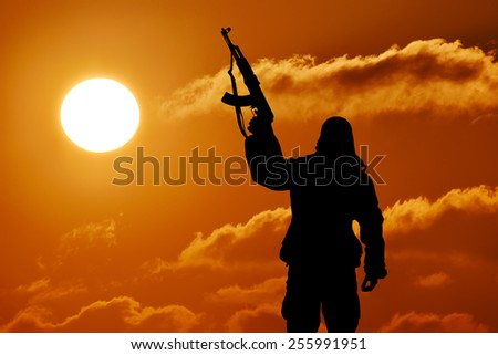 Silhouette of military soldier or officer with weapons at sunset. shot, holding gun, colorful sky, mountain, background - stock photo