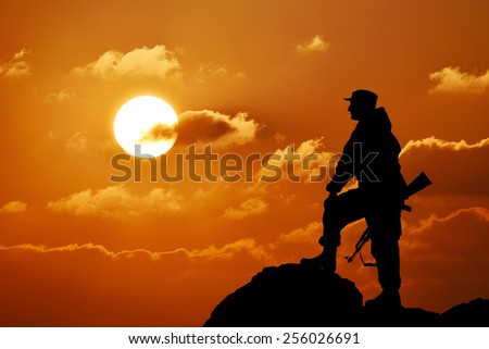 Silhouette of military soldier or officer with weapons at sunset, shot, holding gun, colorful sky, mountain in background - stock photo