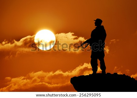 Silhouette of military soldier or officer with weapons at sunset, shot, holding gun, colorful sky, mountain in background. Silhouette of soldier with rifle against a sunset - stock photo