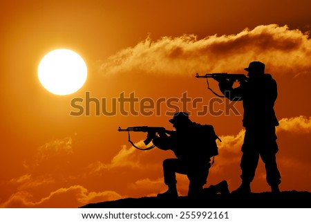Silhouette of military two soldier or officer with weapons at sunset. shot, holding gun, colorful sky, mountain, background, team - stock photo