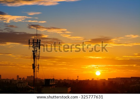 Silhouette of mobile communication antennas in an orange sunset - stock photo