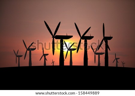 Silhouette of modern wind turbine in a wind farm against a fiery sunset.  - stock photo