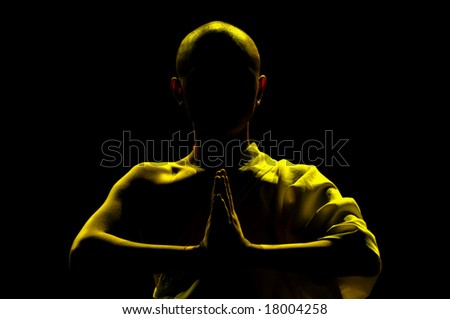 silhouette of monk praying in lotus position - stock photo