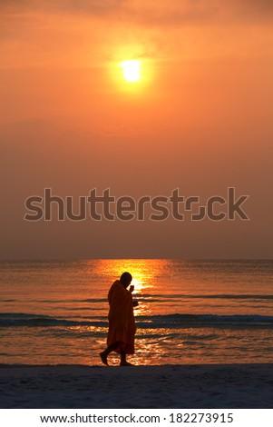 Silhouette of monk walk on the beach , Huahin , Thailand - stock photo
