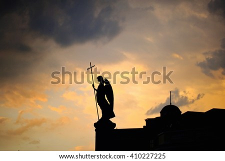 Silhouette of monument with angel on the top of it at sunset. Brest, Belarus - stock photo