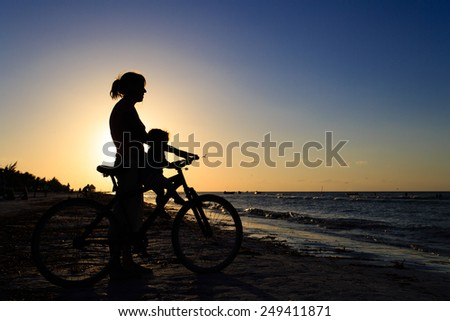 Silhouette of mother and baby biking at sunset sea - stock photo
