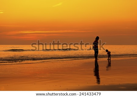 Silhouette of mother and l baby on sunset beach