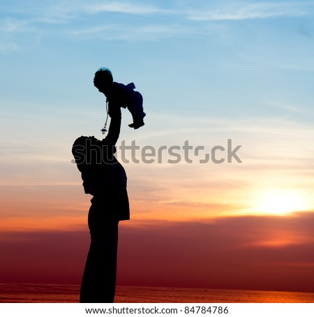 silhouette of mother playing with her child - stock photo
