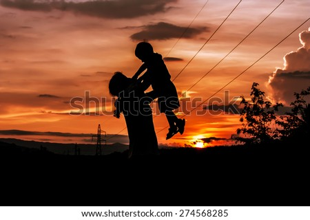 silhouette of mother playing with her son at Mountains and high voltage poles sunset background - stock photo