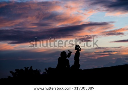 Silhouette of mother raised the baby up in the air.