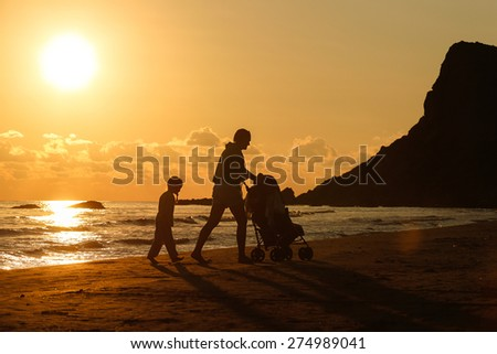 Silhouette of mother walking with her daughter and baby, pushing a stroller on a sandy beach in late summer, enjoying the evening chill. Family vacation, traveling with children concept.  - stock photo