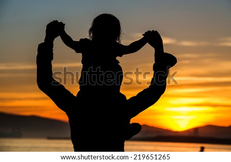 Silhouette of mother which her child against a sunset - stock photo