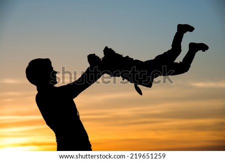 Silhouette of mother which turns her child against a sunset - stock photo
