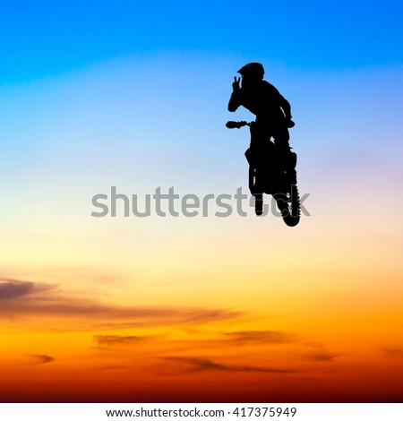silhouette of motocross rider jump in the sky at sunset - stock photo