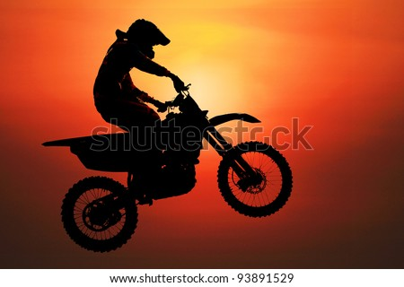 silhouette of motorcycle fly at sunset - stock photo